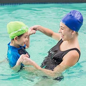 Frau und Kind tragen Bademode der Sanitätshaus Klink und spielen im Pool