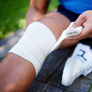 Sportler Bandagiert sich sein eigenes Bein