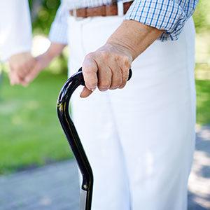 Patient beim halten eines Gehstocks